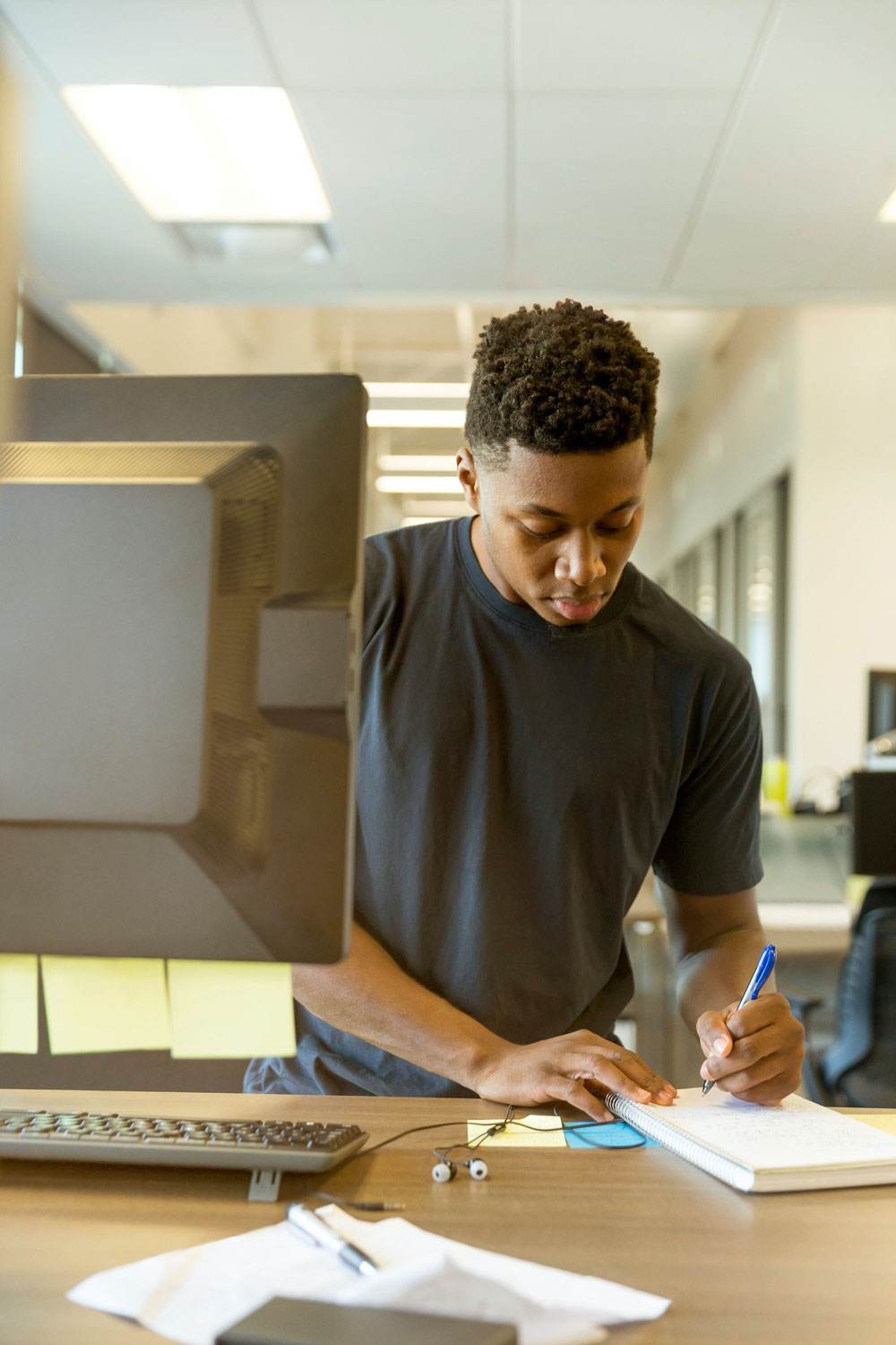 Young man working at a desk on a computer writing something down