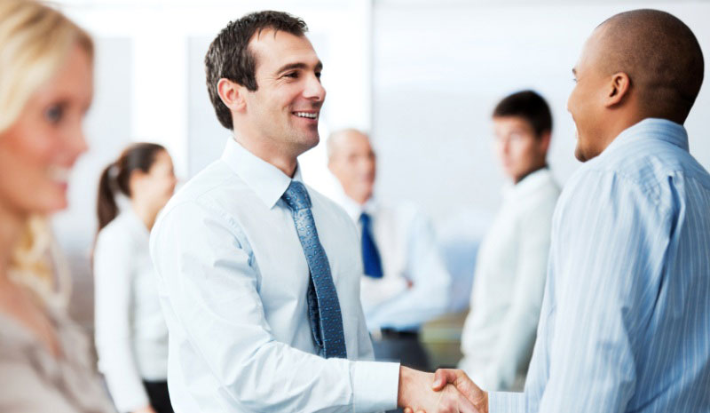 Men in formal clothing smiling and shaking hands